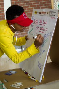 Student adding core value to flip chart