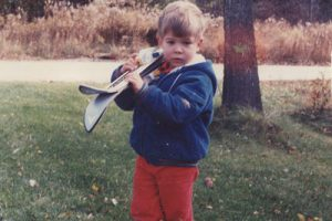 Ryan holding skis at 2 years old